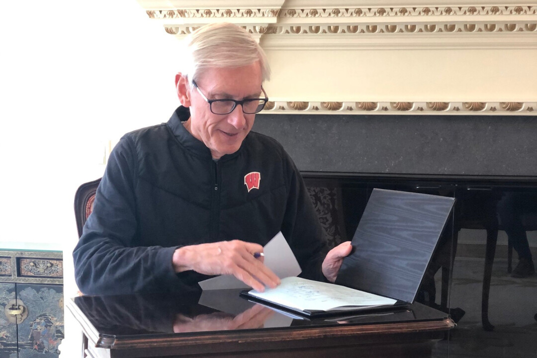 Wisconsin Gov. Tony Evers signs COVID-19 legislation on April 15, 2020.