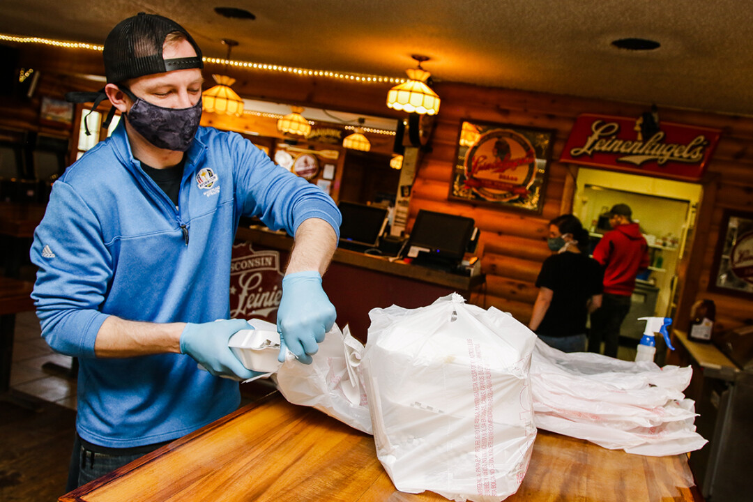 An employee at Loopy's Saloon & Grill outside Chippewa Falls prepares an order for delivery.